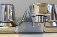 Dripping Faucet. Bathroom faucet dripping and wasting water Royalty Free Stock Images