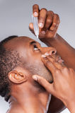 Dripping his eyes with eye drops. Stock Photos