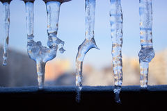 Dripping icicles against the sky. transparent icicle close up ag Royalty Free Stock Photos
