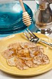 Dripping maple syrup over a stack of Johnny cakes. Dripping maple syrup over a stack of homemade Johnny cakes  sprinkled with powdered sugar on a round, yellow Royalty Free Stock Images