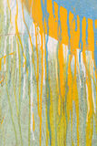 Dripping paint on cracked wood. Abstract spattered yellow and blue paint drips down cracked wood background texture Stock Photography