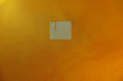 Dripping yellow paint on wall. With a lighter square in the center Stock Photography