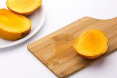 Drittel einer Mango und seines Juice On Wooden Boards Lizenzfreies Stockfoto