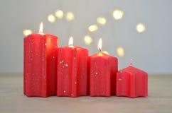Drittes Adventssonntag Vier rote Kerzen Drei Weihnachtskugeln getrennt auf Weiß stockfotografie