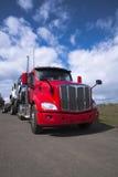 Driva den röda halva lastbilen för den stora riggen som transporterar på en andra halva lastbilar Royaltyfria Bilder