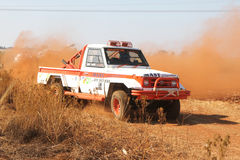 Driva den vita Toyota Landcruiser lastbilen som upp sparkar damm på vänd Arkivbild