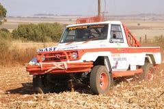 Driva den vita Toyota Landcruiser lastbilen som upp sparkar damm på vänd Royaltyfria Foton