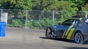 Driva händelsen, djärva män utför ett extremt trick på asfaltarenan framme av allmänhet bak metallstaketet stock video