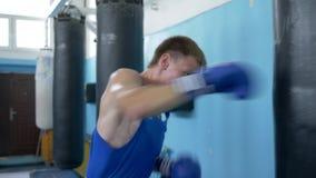 Driva utbildning, brottare som mannen utarbetar boxareslag på att stansa påsen för mästerskap på sportklubban lager videofilmer