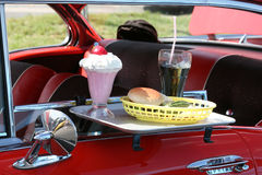 At the Drive In. Sundae, Burger and Soft Drink on a tray on a 50's era car.  A common scene in a bygone time Stock Images
