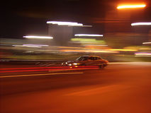 Drive-by. Nightshot of a car in motion followed with camera. Background with lights royalty free stock images