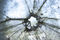 Drive by. A Bullet hole in an old car window Stock Image