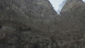 We drive along the road in a deep ravine in foggy weather, examining the rocks stock video footage