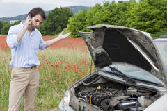 Drive breakdown. Man calling the repair service after car breakdown Stock Photography