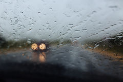 Drive car at heavy rain. Water drops at window Stock Photos