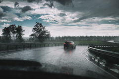 Drive car in rain on curve asphalt wet road. Drive car in the rain on curve asphalt wet road Royalty Free Stock Photography