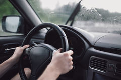 Drive car in rain. Hands on steering wheel Royalty Free Stock Image