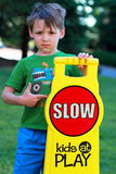 Drive Careful sign with small boy. A closeup of a somber little 5 yr old boy in green shirt and disheveled dark hair pointing to a \kids at play\ sign. Shallow Royalty Free Stock Image