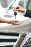 Drive carefully! Close-up shoot of the car salesman hand giving Royalty Free Stock Photography
