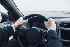 Drive carefully!. Close up of man keeping hands on the steering wheel while driving a car royalty free stock photography