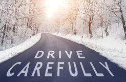 Drive carefully. Empty road in forest in winter with drive carefully text stock image