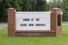 Drive Carefully Sign. A sign on the town green informs drivers to drive carefully since school is out. Easily add your own message stock photo