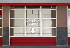 "Drive In Claims. Insurance Adjuster building garage door with ""Drive In Claims"" on door window. People can drive their vehicles in and get accident repair Royalty Free Stock Image"
