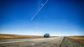 Drive in the desert. I was traveling to Mongolia, in the daytime and our car is stuck in the middle of the desert with blue sky and one plane pass too Stock Photography