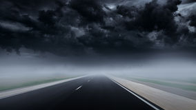 Drive at empty asphalt road to thunderstorm through mist Royalty Free Stock Image
