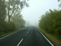 Drive on fog road. Fog on the road. Safe drive in fog. Drive careful stock photography