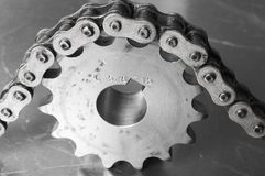 Drive-force idea. Cog, gear, driven by large chain in black/white Stock Photos