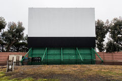 Drive in movie area with screen and speaker poles Royalty Free Stock Photo