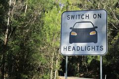 Drive with precaution. A road signage asking motor drivers to switch on headlights for save driving on curved roads Royalty Free Stock Images