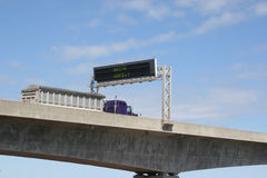 Drive Safely. Truck driving over the Confederation Bridge and under a 'Drive Safely' sign royalty free stock image