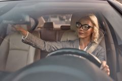 Free Drive Safely. Beautiful Business Woman In Eyeglasses Sitting On The Front Seat Of The Car And Adjusting Rear-view Mirror Stock Images - 166134894