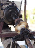 Drive shaft of a water pump on a large size ball bearing support and universal joint with dark dirty grease on running Royalty Free Stock Photos