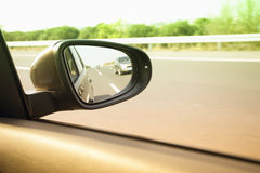 Drive in sunshine. Car and rear view mirror on the road Royalty Free Stock Photos