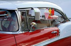 Drive Thru Meal. Old classic car with burger order on window Royalty Free Stock Photography