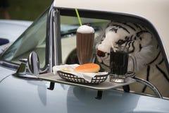 Drive up window service. Stuffed animal receiving drive up window service in a classic car Stock Image