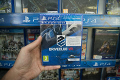Driveclub VR. Bratislava, Slovakia, circa april 2017: Man holding Driveclub VR videogame on Sony Playstation 4 console in store Stock Image