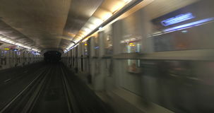 Driveless underground trains on the route. View from moving underground train which leaving the tunnel and arriving to the platform with automatic sliding doors stock video footage
