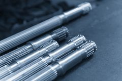 The driven shaft with the teeth for mechanical purpose. The metal spline shaft manufacturing Royalty Free Stock Images