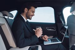 Driven by success. Handsome young man in full suit working using laptop while sitting in the car royalty free stock image