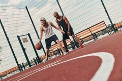 Driven to win. Two young men in sports clothing playing basketball while spending time outdoors stock image
