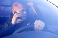 Driver. The driver drives the car looking through glass speaks by phone Royalty Free Stock Image