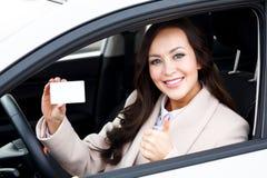Driver abbastanza femminile che mostra carta bianca in bianco Fotografia Stock Libera da Diritti