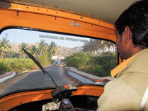Driver of an auto rickshaw taxis on a road Stock Image