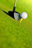 Driver and ball on tee. Close up of golf driver or wood club next to white ball on yellow tee in green grass Royalty Free Stock Photography