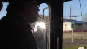 The driver in the cabin of the bus goes on the route smokes while driving. The driver behind the wheel of the bus in the rays of the sun reflected from the side stock video