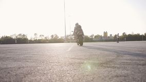 A driver biker with his girlfriend at sunset goes to ride a city on a motorcycle. Slow motion stock footage